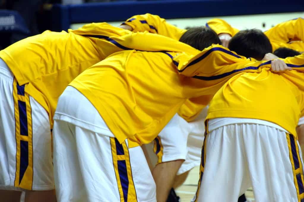 14591662 - high school varsity basketball team huddles together before game start. uniforms are yellow, purple and white.